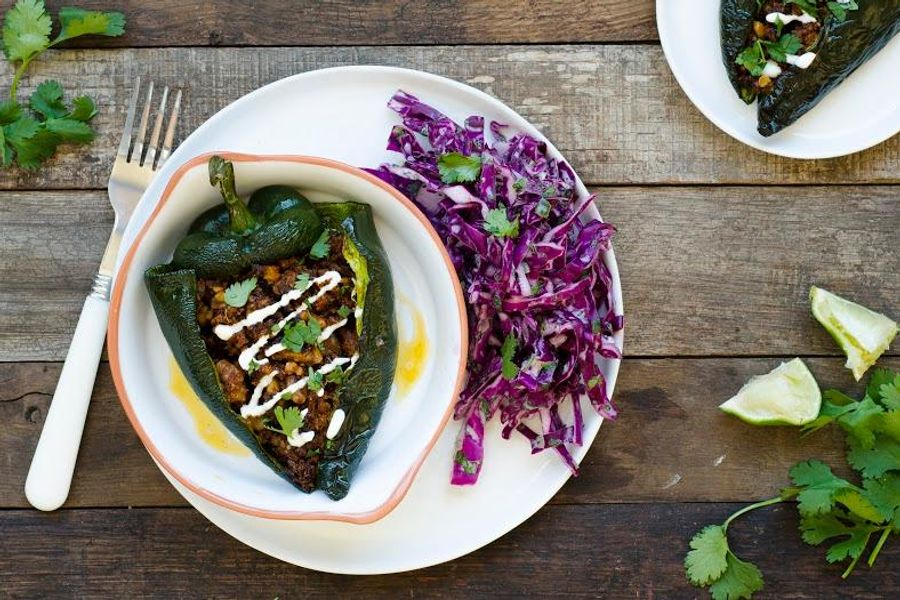 Walnut-stuffed poblano peppers with lime crema and red cabbage slaw