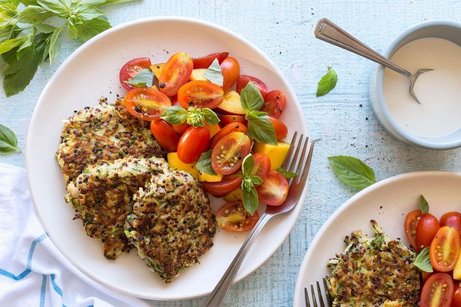 Quinoa-zucchini fritters with tahini dressing and tomato-peach salad