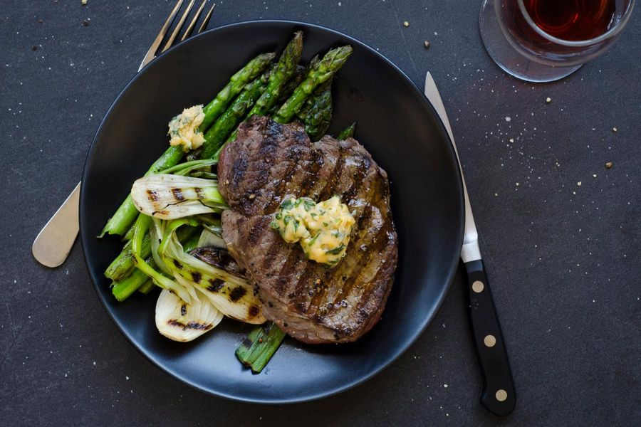 Seared steak with basil butter, asparagus and spring onions