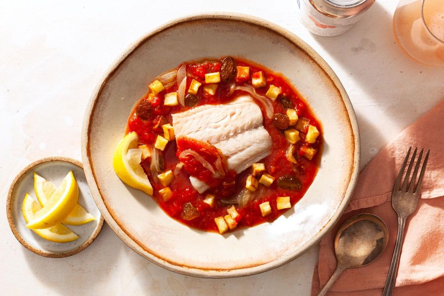 Poached cod in tomato broth with potatoes and raisins