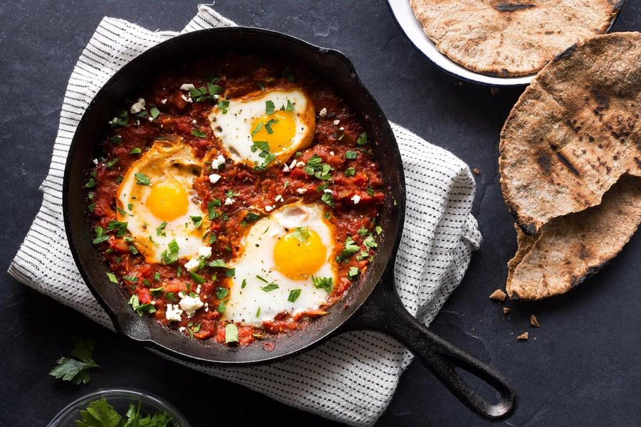 Shakshuka - Eggs in tomato sauce with sauteéd peppers, feta, and pita