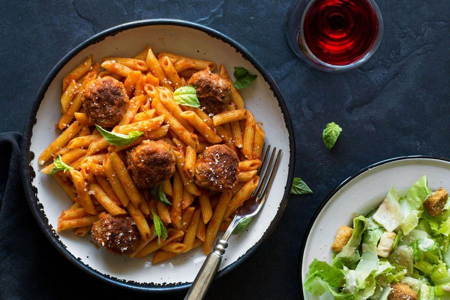 Meatballs and red sauce with penne and Caesar salad
