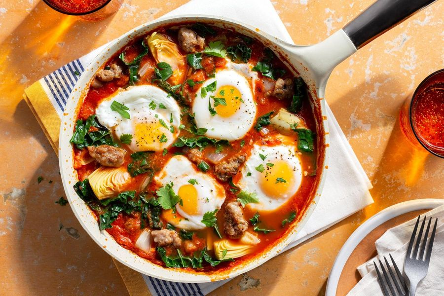 Simple sausage shakshuka with eggs, artichoke hearts, and kale