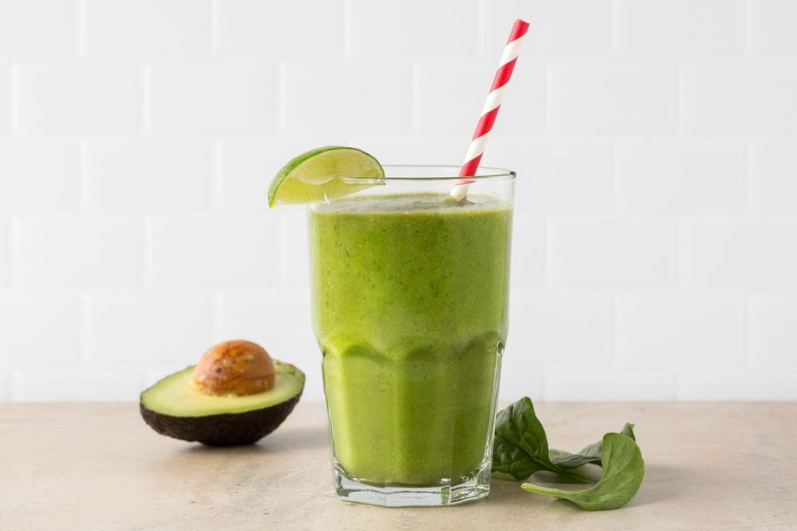 Image of Stress-Beater Smoothie, half an avocado, and a handful of spinach leaves