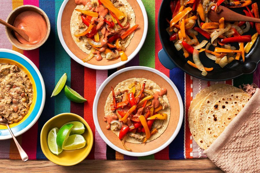 Tex-Mex vegetable fajitas with cheesy refried beans and achiote crema