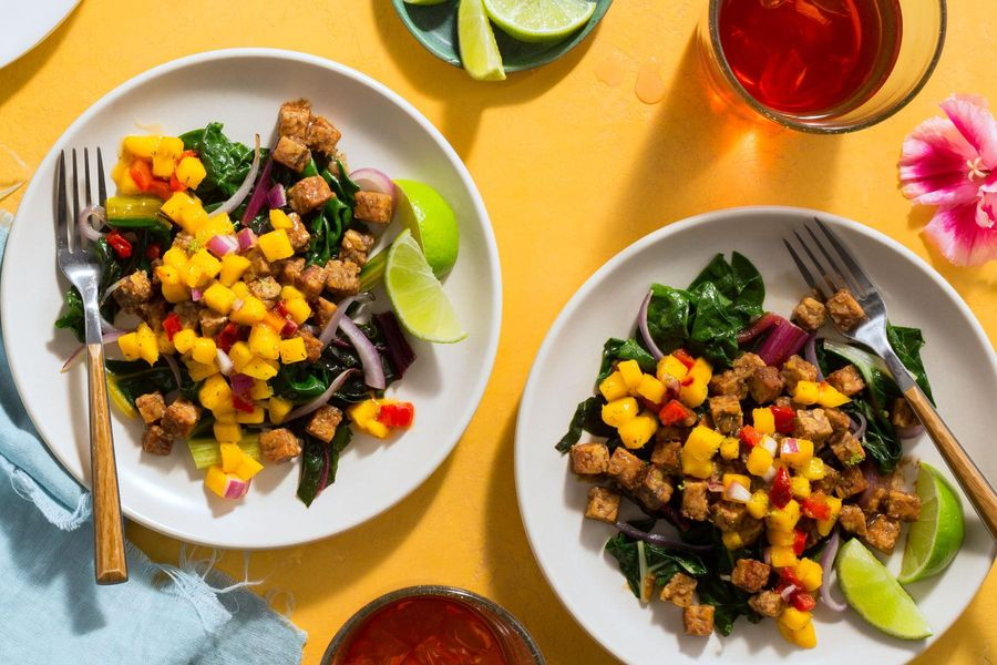 Spicy Jamaican jerk tempeh with sautéed greens and mango salsa