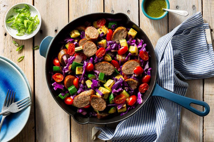 Italian sausages and vegetable skillet with spicy green harissa