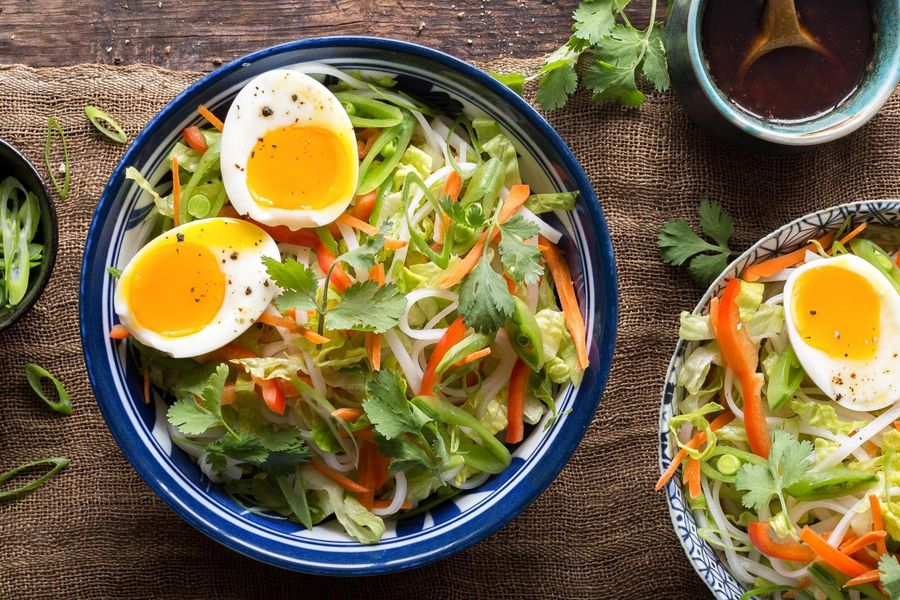 Asian rice noodle bowls with soft-cooked eggs and sesame dressing