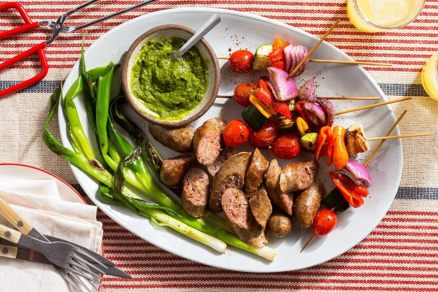 Italian sausages with spicy green harissa and vegetable skewers