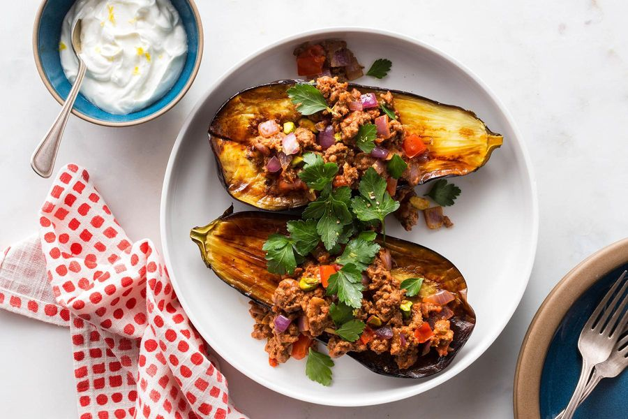 Stuffed eggplant with spiced lamb, pistachios, and lemon-yogurt sauce