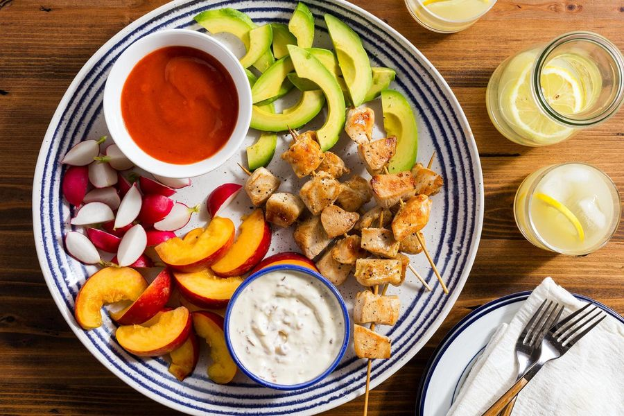 Easy chicken skewers with sliced stone fruit, avocado, and dips