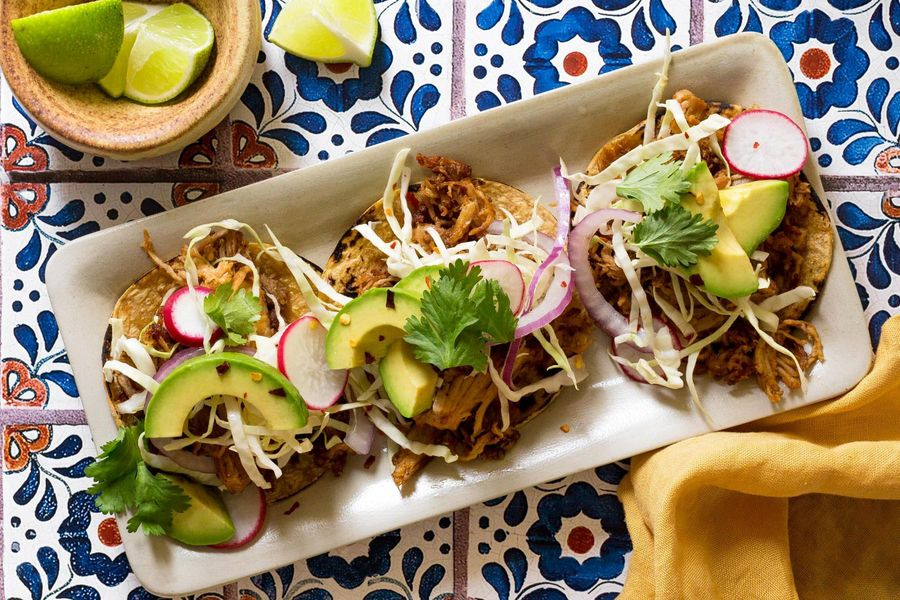 Pork carnitas tacos with avocado and cabbage-radish slaw