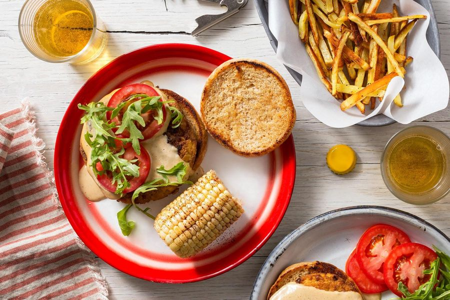 """Cheesy"" tofu burgers with corn on the cob and roasted matchstick fries"