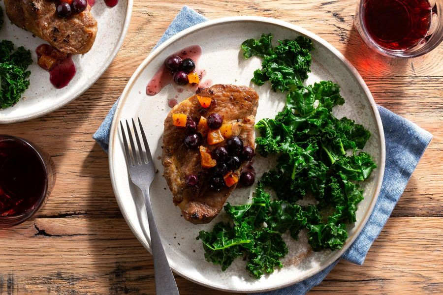 Pork loin chops with blueberry-apricot sauce and sautéed kale