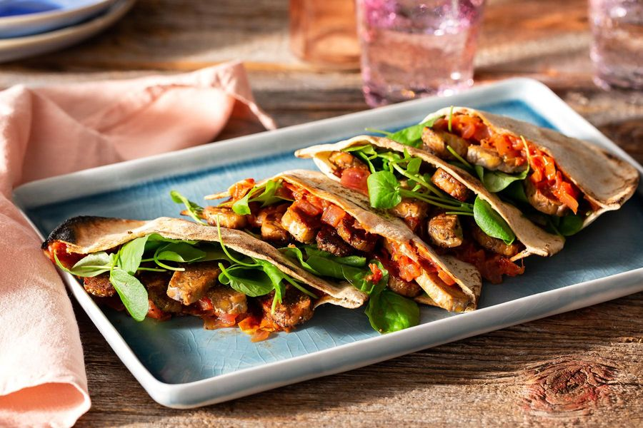 Crispy tempeh pita pockets with greens and tomato-onion jam