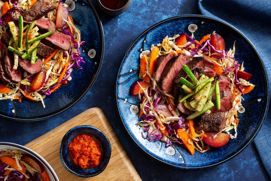 Seared steak over cabbage-plum salad with kimchi vinaigrette
