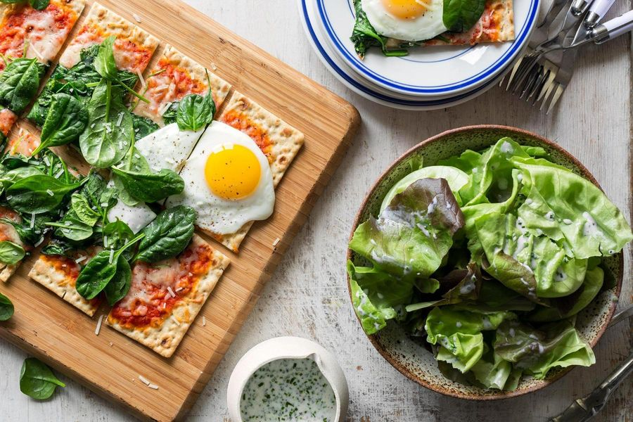 Lavash pizzas with spinach, mozzarella, and fried eggs