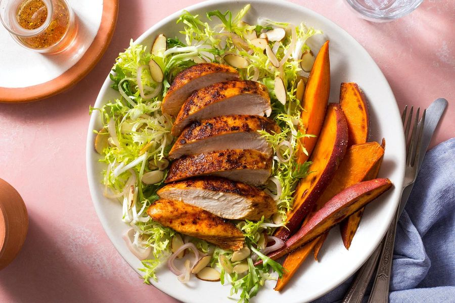 Paprika-spiced chicken with frisée salad and sweet potato wedges