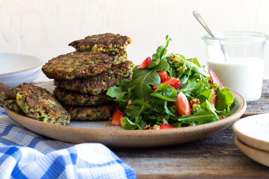 Quinoa fritters with tahini-yogurt sauce and strawberry-arugula salad