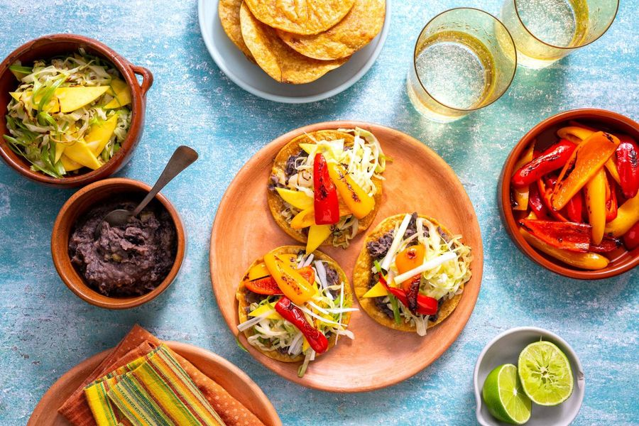 Spicy Jamaican black bean tostadas with sweet peppers and mango slaw
