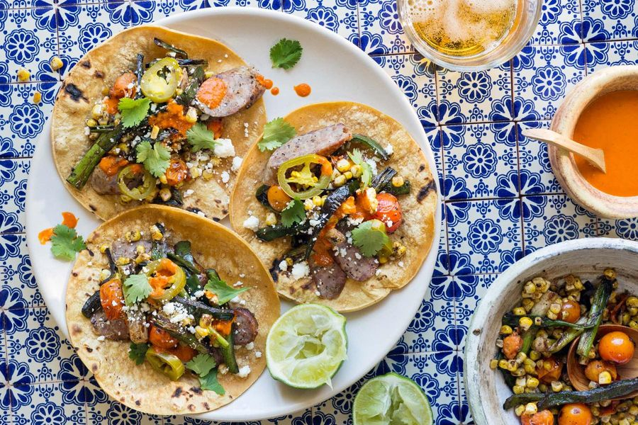 Tacos with Italian sausages, blistered tomatoes, and corn