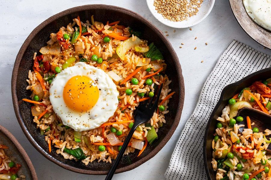 Kimchi fried rice with peas, bok choy, and fried eggs