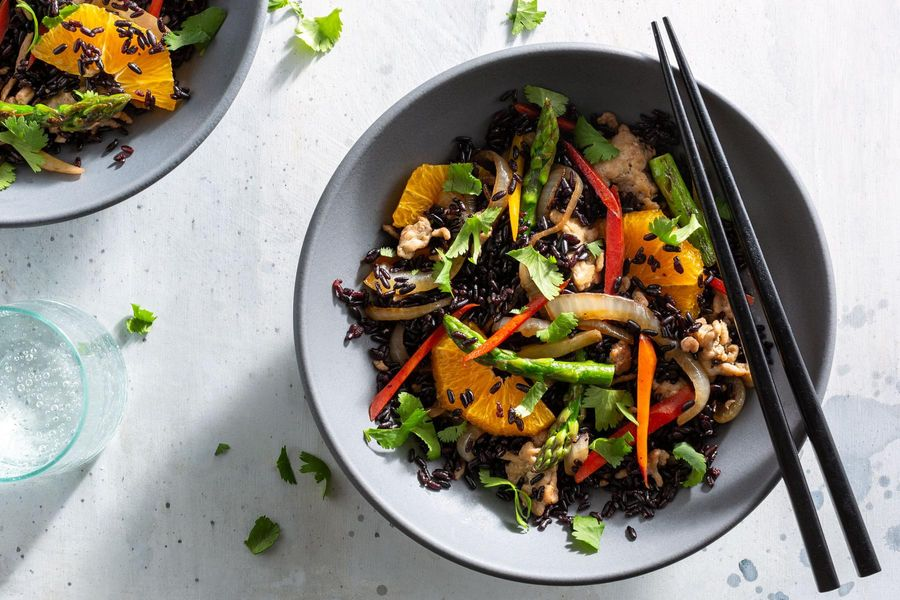 Orange turkey stir-fry with asparagus over black rice