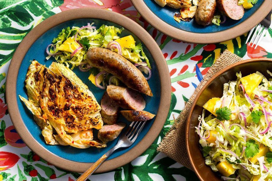 "Pork sausages with cabbage ""steaks"" and pineapple slaw"