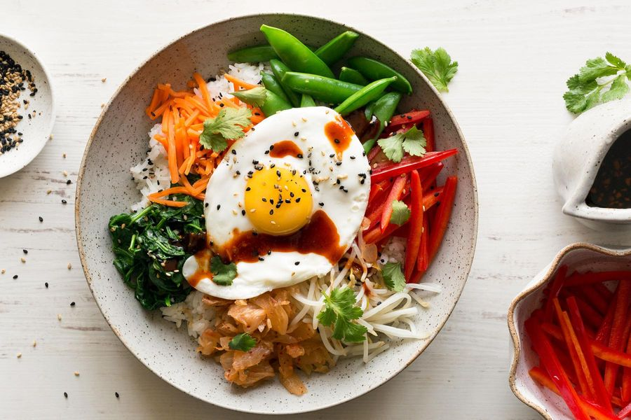 Bibimbap with snap peas, carrots, and fried eggs