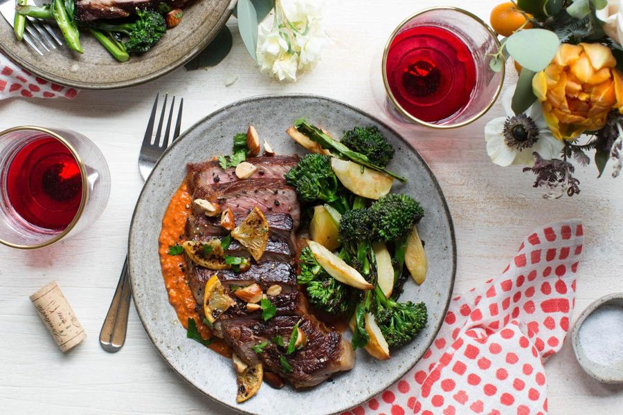 Seared flank steaks with broccolini, roasted parsnips, and romesco