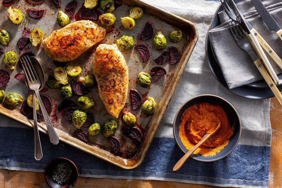Roasted chicken breasts and fall vegetables with romesco
