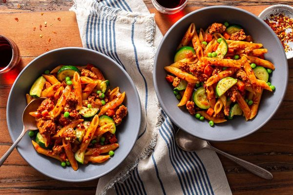 Turkey Bolognese with penne rigate, zucchini, and peas