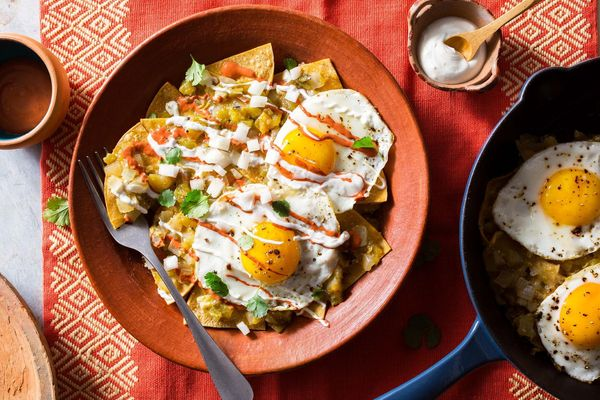 Red, white, and green chilaquiles with fried eggs