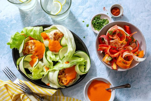 Lettuce-wrapped turkey burgers with spicy chraime carrot salad