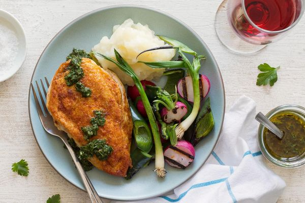 Chicken with yuca mash and grilled radishes, scallions, and poblano