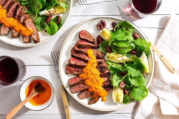 Seared steaks with romesco and artichoke-olive salad