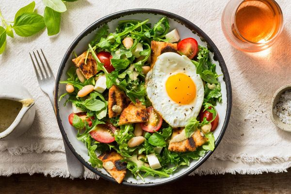 White bean panzanella salad with mozzarella and fried egg