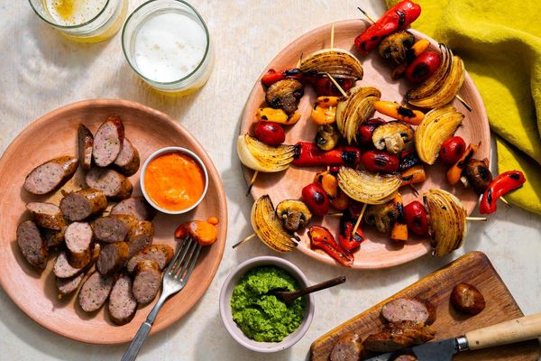 Italian sausages and vegetable skewers with two romescos